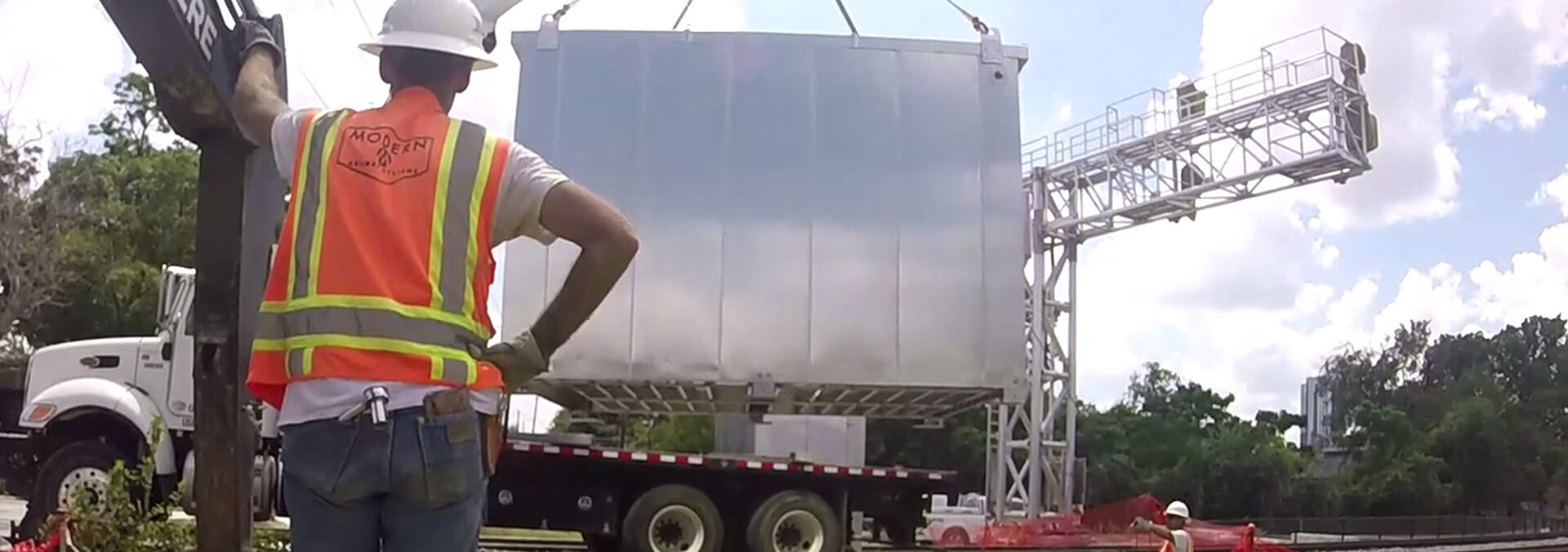 A construction worker unloading steel structure from semitruck.
